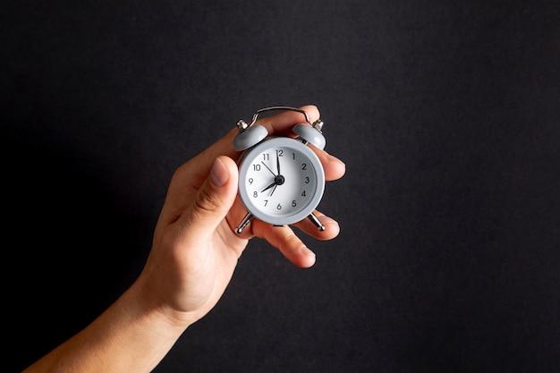 Mano sosteniendo un pequeño reloj vintage