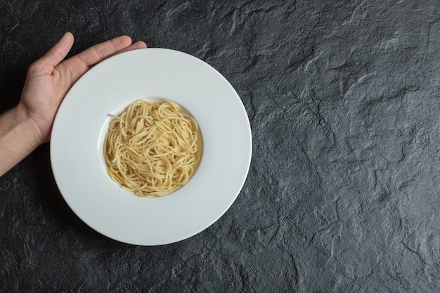 Mano sosteniendo un plato blanco lleno de deliciosos fideos.