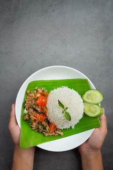 Mano sosteniendo un plato de carne de cerdo picada con arroz de albahaca.