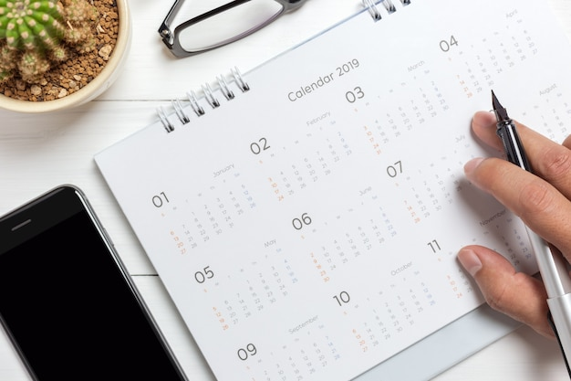 Mano sosteniendo la pluma en el calendario con smartphone y anteojos
