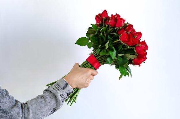 Mano sosteniendo un ramo de rosas rojas aisladas sobre fondo blanco para el aniversario o el concepto de día de san valentín.