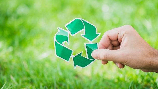 Mano sosteniendo reciclar símbolo contra la hierba verde