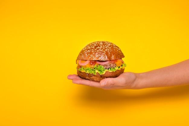Mano sosteniendo sabrosa hamburguesa de ternera