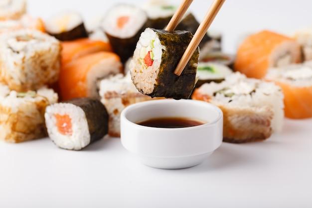 Mano sosteniendo sushi salmon roll en palillos con espacio de copia para trabajos de diseño