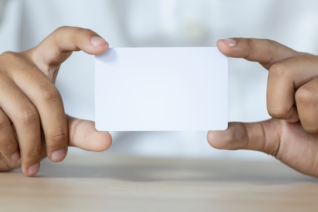 Mano sosteniendo la tarjeta blanca vacía