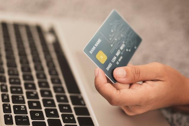 Mano sosteniendo una tarjeta de crédito junto a una computadora portátil
