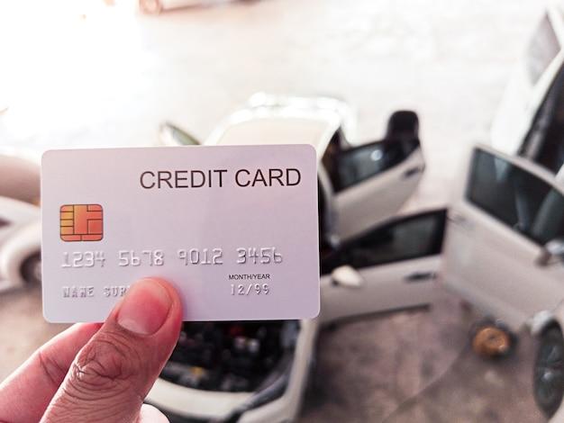 Mano sosteniendo una tarjeta de crédito en el taller de reparación de automóviles