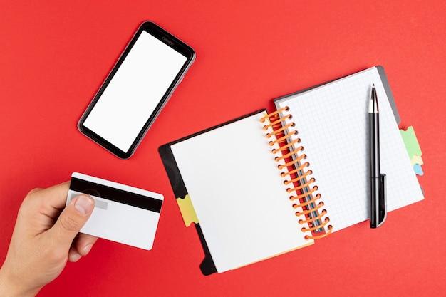 Mano sosteniendo una tarjeta junto a un cuaderno y teléfono simulacro