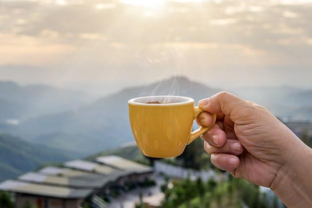Mano sosteniendo una taza blanca de tazas de café espresso caliente y vista a la naturaleza del paisaje de montaña en la mañana con la luz solar