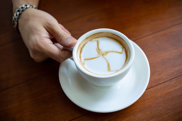 Mano sosteniendo la taza de café caliente