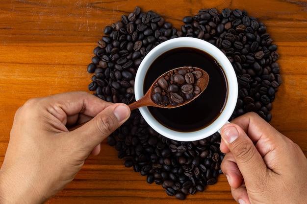 Mano sosteniendo una taza de café negro con granos de café