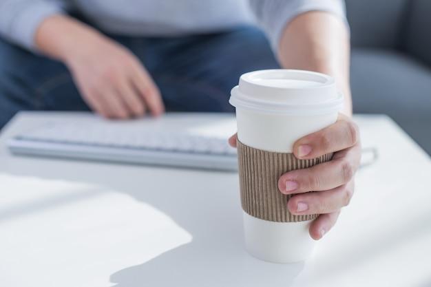 Mano sosteniendo la taza de café o el té y la tableta digital teclado elegante del muelle, pluma de la aguja en la mesa de madera, efecto del filtro