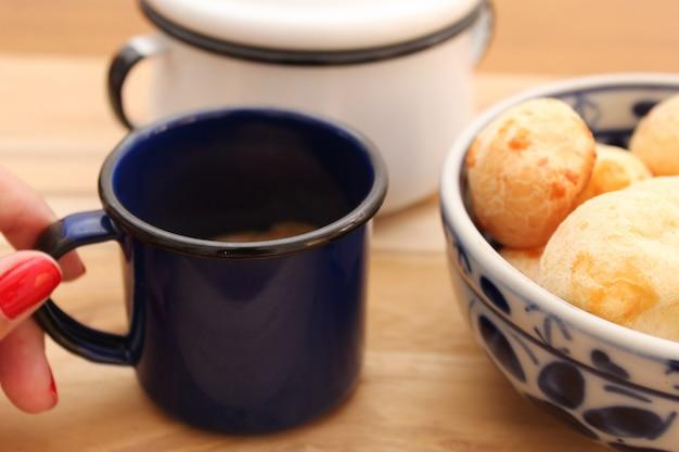 Mano sosteniendo una taza de café vintage y un tazón de pan de queso brasileño (pão de queijo) sobre la mesa.