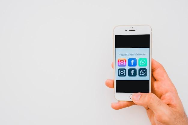 Mano sosteniendo teléfono con aplicaciones populares y espacio para copiar