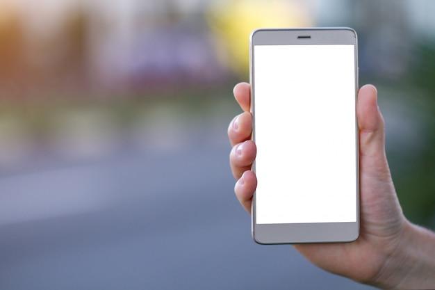 Mano sosteniendo un teléfono móvil con pantalla en blanco en la calle