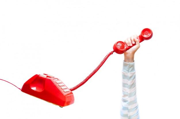 Mano sosteniendo teléfono rojo