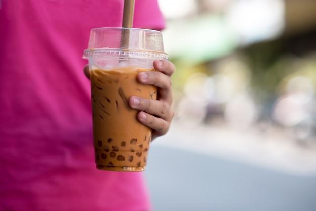 Mano sosteniendo un vaso de plástico de taiwán helado de té con leche burbuja con fondo de desenfoque,