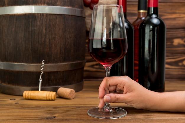 Mano sosteniendo vaso de vino con botellas y barril