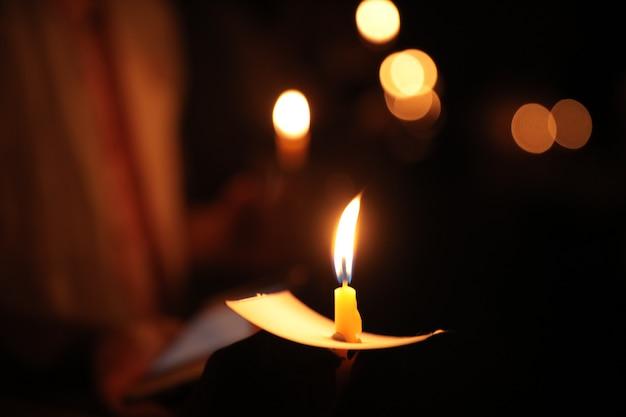 Mano sosteniendo una vela en la noche con bokeh en la oscuridad