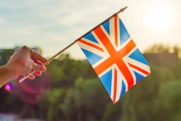 Mano sostiene bandera de gran bretaña en una ventana abierta