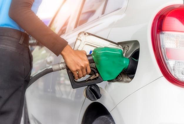 La mano sostiene la boquilla de combustible para agregar combustible al automóvil en la estación de servicio