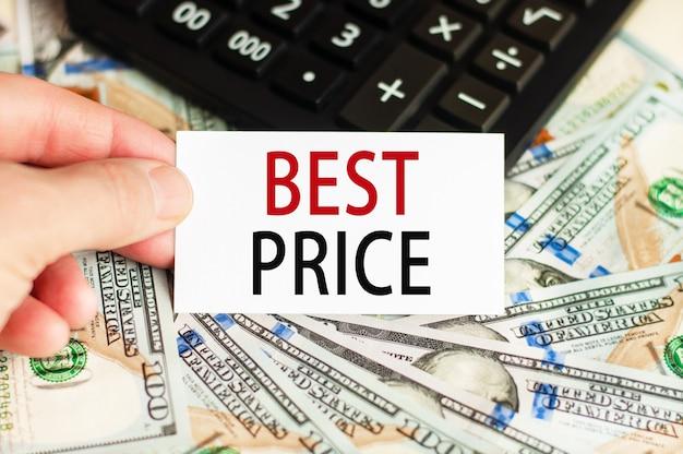 Una mano sostiene un cartel con la inscripción - mejor precio en el fondo de los billetes y una calculadora sobre la mesa.