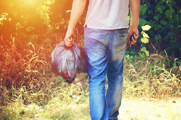 Mano sostiene contra el bosque lleno de basura bolsa de plástico negro