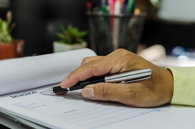 Mano sostiene la factura de trabajo de pluma y papel en el escritorio.