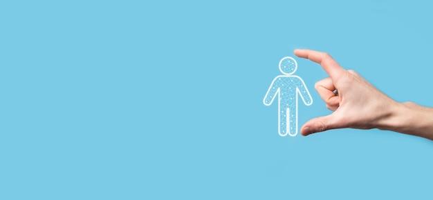 La mano sostiene el icono de la persona del hombre en el fondo de tono oscuro. recursos humanos, icono de la gente. concepto de estructura organizativa.