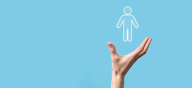 La mano sostiene el icono de la persona del hombre en la superficie de tono oscuro