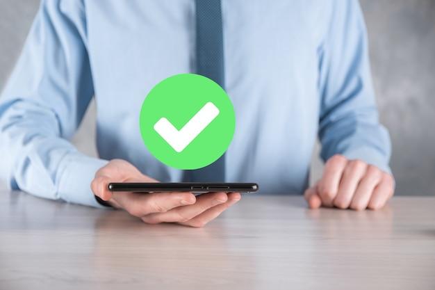 La mano sostiene el icono verde marca de verificación, signo de marca de verificación, icono de tick, signo de la derecha, botón de marca de verificación verde del círculo, listo. sobre fondo oscuro. bandera. espacio de copia. lugar para el texto.