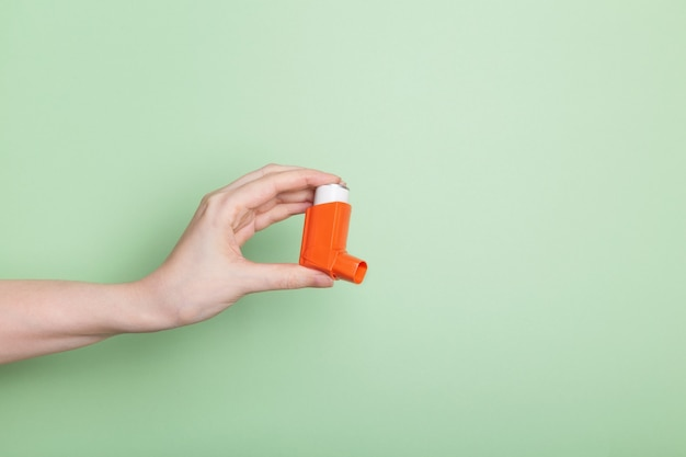 La mano sostiene el inhalador naranja para tratar el asma aislado sobre fondo verde claro