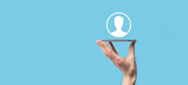 La mano sostiene la interfaz del icono de la persona del usuario sobre fondo azul. símbolo de usuario para el diseño de su sitio web, logotipo, aplicación, interfaz de usuario.
