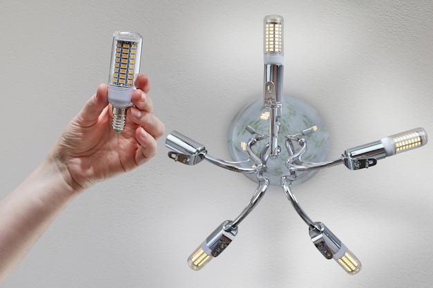 La mano sostiene la lámpara de maíz led para el hogar antes de la instalación en la lámpara de techo cromada.