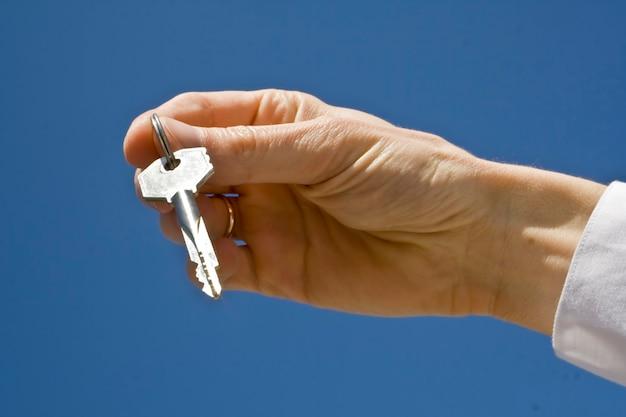 Mano sostiene una llave (llave en foco)