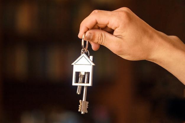 La mano sostiene las llaves del apartamento o casa.
