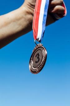 Una mano sostiene una medalla de bronce en tercer lugar, con el cielo de fondo. concepto de victoria
