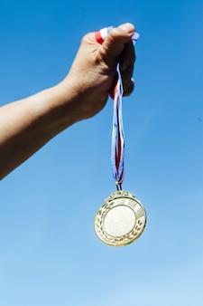 Una mano sostiene una medalla de oro de primer lugar, con el cielo de fondo. concepto de victoria