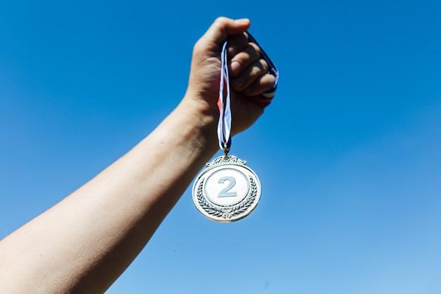 Una mano sostiene una medalla de plata en segundo lugar, con el cielo de fondo. concepto de victoria