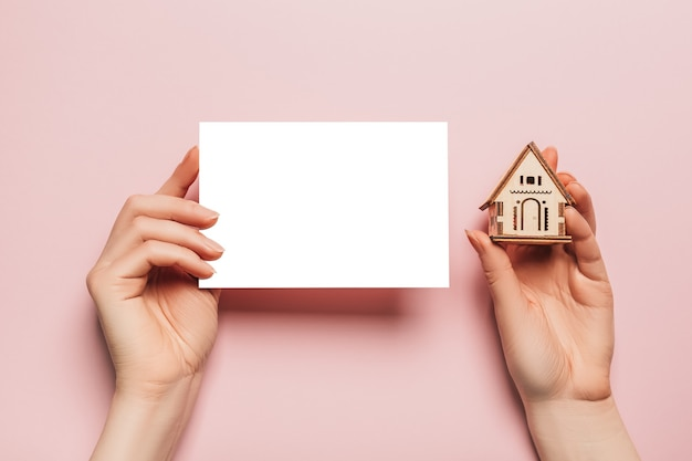 La mano sostiene el modelo en miniatura de la casa con un espacio en blanco en un espacio rosa