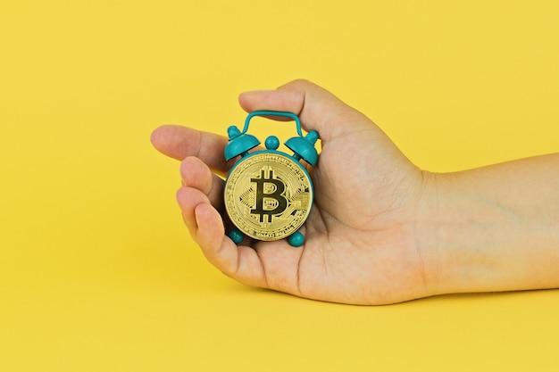 Mano sostiene pequeño despertador con bitcoin.
