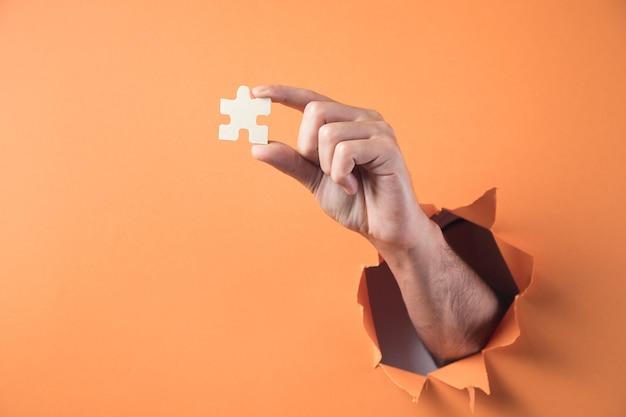 Mano sostiene la pieza del rompecabezas sobre fondo naranja