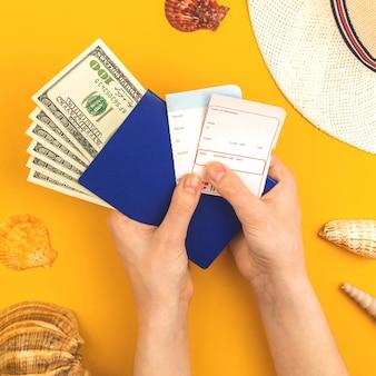 La mano sostiene la tarjeta de embarque de la aerolínea para viajes de verano y fondo de concepto de vacaciones con pasaporte, dinero y conchas marinas, vista superior