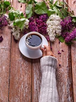 La mano sostiene una taza de café de la mañana con ramas de flores lilas de primavera floreciendo sobre fondo de madera vista desde arriba. estilo subterráneo endecha plana.