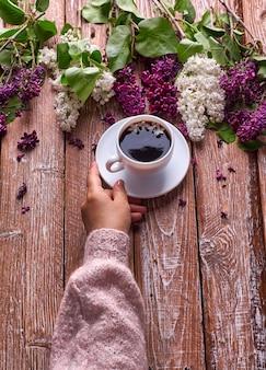 La mano sostiene una taza de café de la mañana con ramas de flores lilas de primavera floreciendo sobre fondo de madera vista desde arriba.