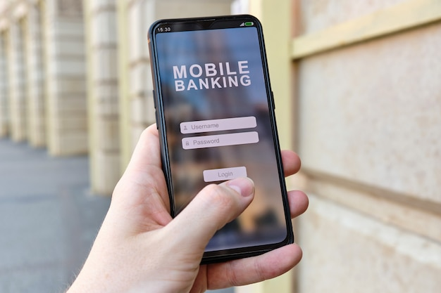 La mano sostiene el teléfono inteligente con la banca móvil y la interfaz de autorización de inicio de sesión y contraseña