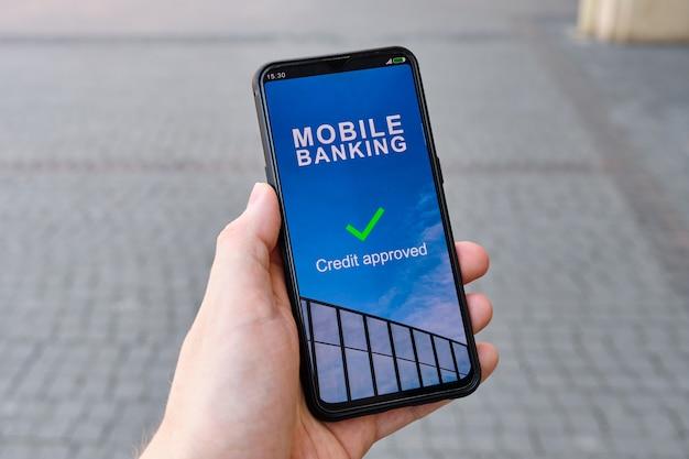 La mano sostiene el teléfono inteligente con crédito de interfaz de banca móvil aprobado