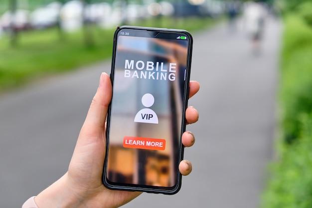 La mano sostiene el teléfono inteligente con interfaz de banca móvil y haga clic para obtener más información sobre el estado vip