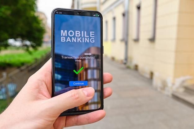La mano sostiene el teléfono inteligente con la interfaz de banca móvil y la transacción de inscripción completa.