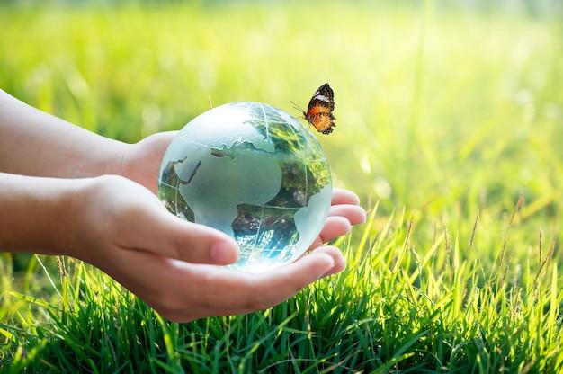 Mano sujetando una bola de tierra de cristal con una mariposa sobre fondo de hierba verde